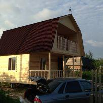 Дом из бруса с балконом и ломаной крышей